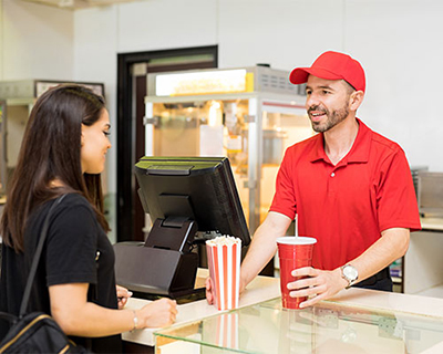 Male concessions stand worker handing female customer a drink and popcorn in front of register