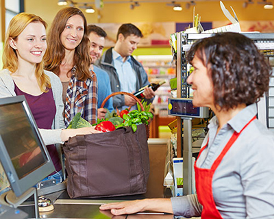 Female cashier smiling at two men and two women standing in check-out line at grocery store