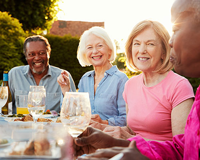 Four smiling senior adults sitting at an outside table eating and drinking