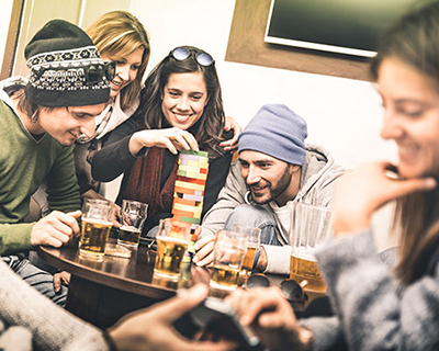 Five smiling young adults sitting around table playing board game Jenga and having beers